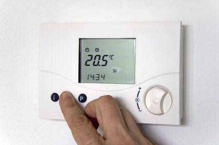 Regolare il termostato di un sistema di riscaldamento a mano Archivio Fotografico - 6612151