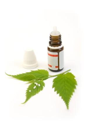 homeopatia: p�ldoras de gl�bulo homeop�ticos y hoja aislados en blanco