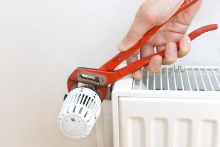 alicates: mano de aplumber con unos alicates y radiador Foto de archivo