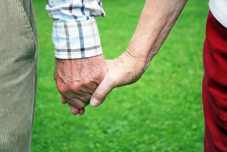 緑の背景と手を繋いでいる年配のカップル 写真素材