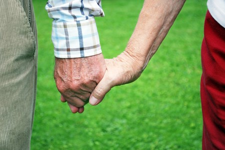 senior couple holding hands with green background Stock Photo