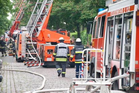 german firemen with fire engine and aerial ladder photo