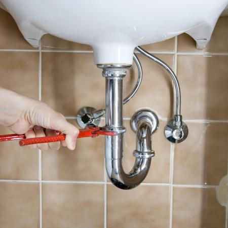 fontanero: mano de un fontanero fijar un drenaje