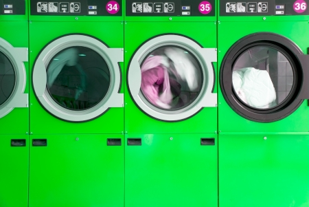 green clothes washers in a laundrette