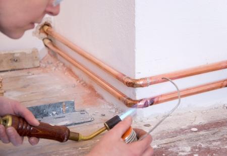 koperen leiding: hand van een loodgieter met de soldeer bout en koperen leidingen