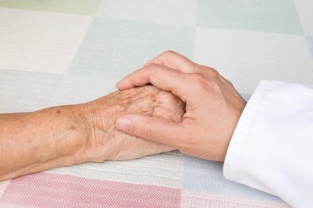 Hand eines Arztes an der Hand eines älteren Patienten