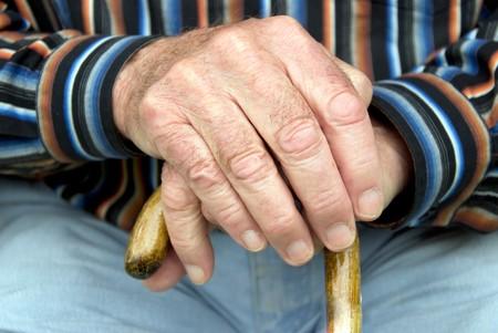 杖を保持している年配の男性人の手 写真素材