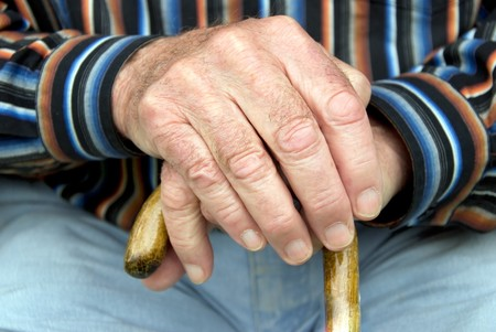 retirement age: hand of a senior man holding a cane