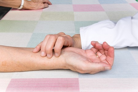 lonelyness: hand of a physician, measuring the pulse rate of a senior patient Stock Photo
