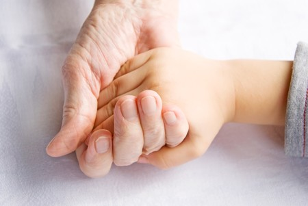 grandkids: hand of a child and ahand of a senior woman