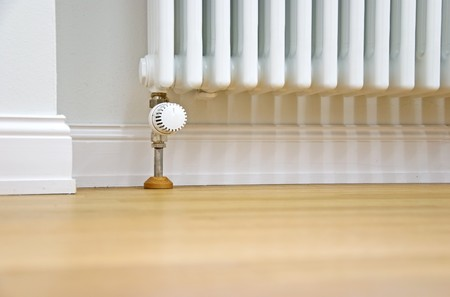 modern radiator at the wall and parquet floor Standard-Bild