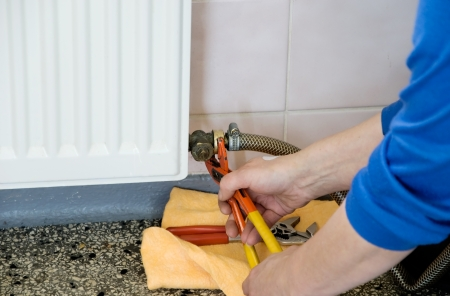 hands of a plumber repairing a gas heating Stock Photo