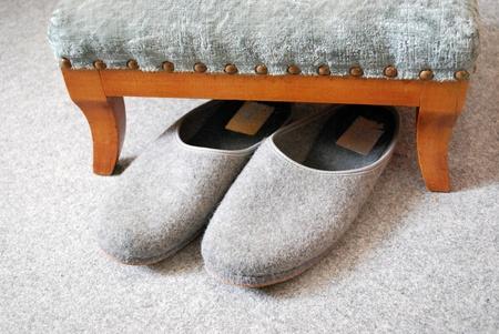 スツールとカーペットの上の古い灰色スリッパ 写真素材