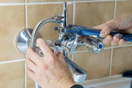 desague: manos de un plomero con llave arreglar un grifo