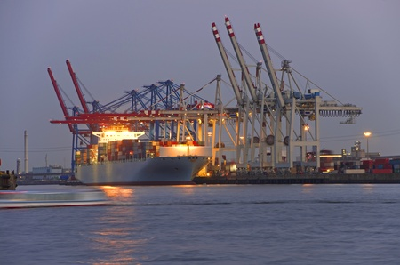 containership: big container ship at the hamburg harbor at sunset