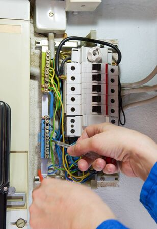 hands of an electrician measuring electrical cables photo