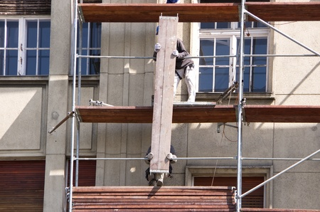 constrution site: scaffold builder at the facade of an old building