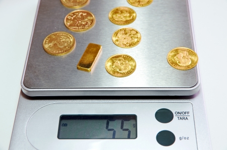 gold bar an coins on a scales photo