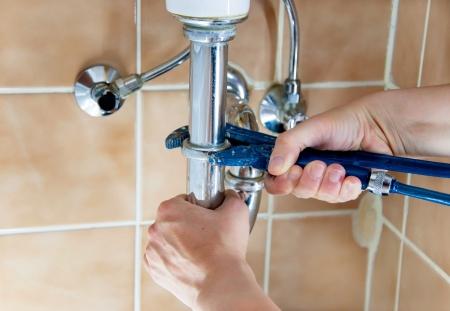 mains d'un plombier avec évier et clé