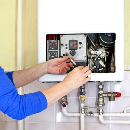 and heating: repairman fixing a gas heating with screwdriver Stock Photo