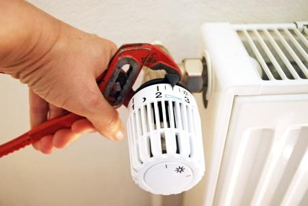 Idraulico che fissa un radiatore con pontili Archivio Fotografico - 20414483