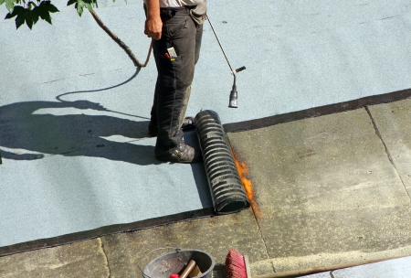 waterproofing: roofer with a gas burner on a roof