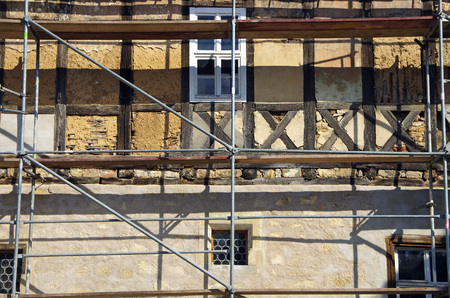 renovate old building facade: half-timbered house under monument protection with construction site in germany