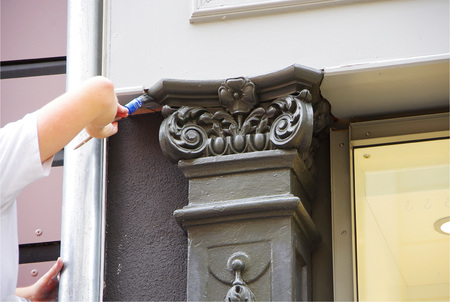 painter restaurating a historical facade in germany photo