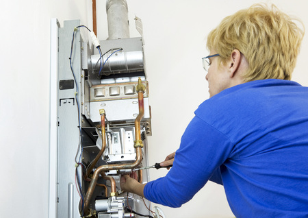 emissions: plumber installing a new gas heating at the wall