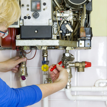 repairman fixing a gas heating with screwdriver photo