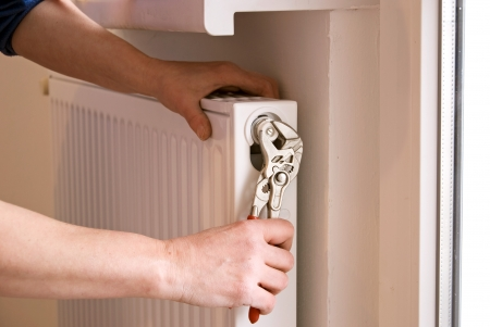 radiator: plumber fixing a radiator with pliers on a construction site