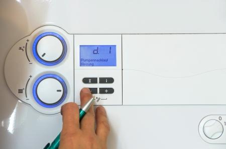 Mani di un idraulico regolando una caldaia a gas Archivio Fotografico - 23717136