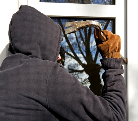 burgler: housebraker with tool trying to open window