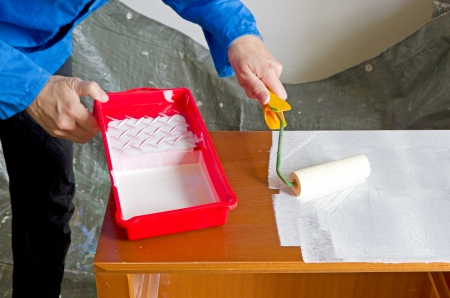 priming paint: painter with paint roller painting a wooden commode