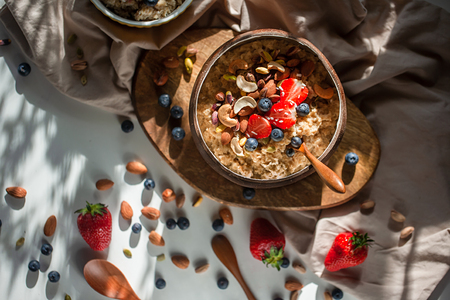 Oatmeal porridge in coconut bowl with wooden spoon on natural wooden tray. Porridge oats with strawberry, pistachios, blueberry, almond and banana. Shadow of sunrise morning. Top view or flat lay