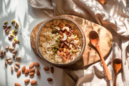 Oatmeal porridge in coconut bowl with wooden spoon on natural wooden tray. Porridge oats with almonds, pistachios and other nuts. Shadow of sunrise morning. White background. Top view or flat lay. Stock Photo