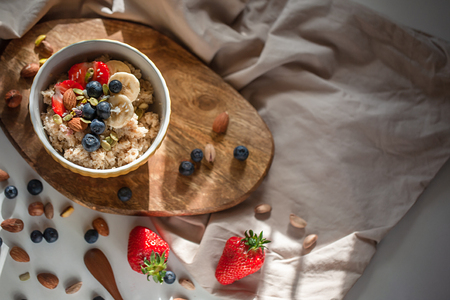 Oatmeal porridge in yellow dish with fruits and nuts on natural wooden tray. Porridge oats with strawberry, pistachios, blueberry, almond and banana. Shadow of sunrise morning. Top view or flat lay