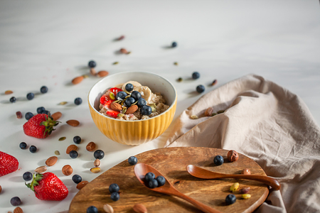 Oatmeal porridge in yellow dish with fruits and nuts on natural wooden tray. Porridge oats with strawberry, pistachios, blueberry, almond and banana. Shadow of sunrise morning. Side view