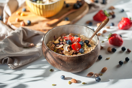 Oatmeal porridge in coconut bowl with wooden spoon. Porridge oats with strawberry, pistachios, blueberry, almond and banana. Shadow of sunrise morning. White background. Side view