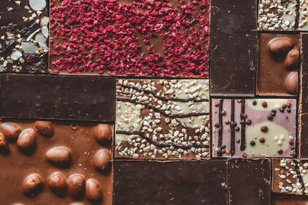 Background with milk, dark and white chocolate bar pieces. Chocolate pazl with hazelnut, peanut, dried raspberries and raisins