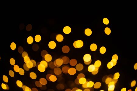 Bright golden glitter festive background. Abstract shimmering circles decorative backdrop. Bokeh lights with shiny effect. Overlapping glowing and twinkling spots.