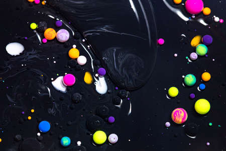 Fluid art texture. Background with abstract mixing paint effect. Liquid acrylic picture with flowing bubbles. Mixed paints for posters or wallpapers. Black and colorful overflowing colors