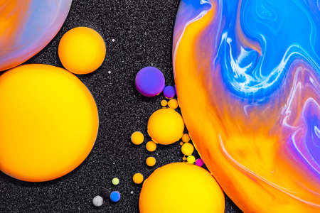Fluid art texture. Abstract backdrop with mixing paint effect. Liquid acrylic artwork that flowing bubbles. Mixed paints for posters or wallpapers. Black and vibrant overflowing colors