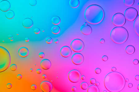 Creative neon background with drops. Glowing abstract backdrop with vibrant gradients on bubbles. Multicolor overflowing picture