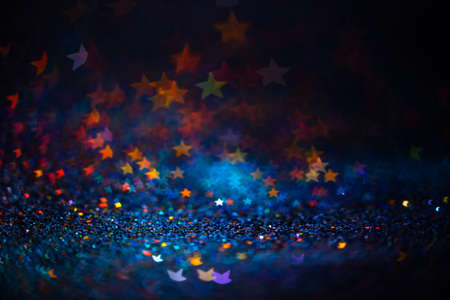 Festive twinkle lights background, abstract sparkle backdrop with stars, modern design overlay with sparkling glimmers. Blue, orange and green backdrop glittering sparks with blur effect 免版税图像