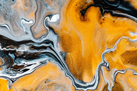 Fluid art texture. Abstract background with iridescent paint effect. Liquid acrylic artwork that flows and splashes. Mixed paints for background or poster. Golden, black and blue overflowing colors Imagens