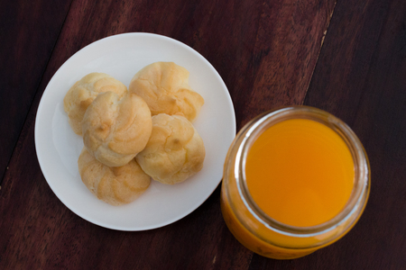 Close up of cream Puffs and orange juice  on wood table photo