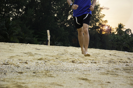 barefooted: Barefooted man running on the Beach at Sunset Stock Photo