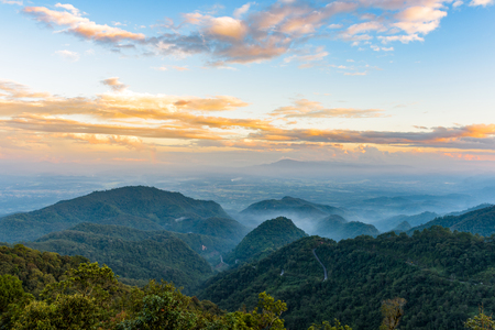 mai: Top view of the mountains, the valley, the road and the forest on a cloudy and golden sky before sunrise at Doi Ang Khang, Chiang Mai, Thailand