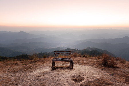 insular: Lonely wooden bench on mountain peak with beautiful skyline